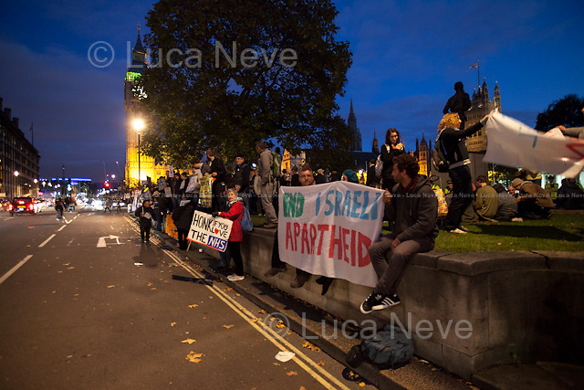 """Day IX - 25.10.2014<br /> <br /> London 17-26.10.2014. A day at the Parliament Square Occupy Democracy Camp in London. Protesters have been camping in Parliament Square since the 17th of October and they will leave on Sunday the 26th. Since the beginning of the direct action protesters have been battling with the MET Police and the Greater London Authority's Heritage Wardens (provided under private contract by AOS Security) over the specific bylaw which applies to a designated area immediately surrounding and including Parliament Square and which bans sleeping equipment. Several people have been arrested, including the Green Party's Baroness Jenny Jones, member of the London Assembly who was later """"de-arrested"""". In the meantime, numerous celebrities, politicians, experts, activists, and members of the public met for conferences and debates about various topics, from democracy to climate change, to the economic crisis, to corruption, to poetry and many more.<br /> <br /> For more information please click here: http://occupydemocracy.org.uk/ & http://on.fb.me/12tuv79"""