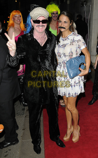 CHRIS EVANS & NATASHA SHISHMANIAN.Freddie For A Day charity gala arrivals, Savoy hotel, the Strand, London, England..September 5th, 2011.full length black suit velvet grey gray flat cap hat sunglasses shades married husband wife dress moustache mustache facial hair blue clutch bag hand v peace sign.CAP/CAN.©Can Nguyen/Capital Pictures.