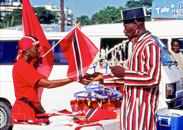 Independence Day Port of Spain, Trinidad. Patriotic man dressed in National Colours tailcoat and boater buying a flag