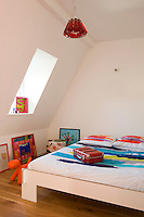 Colourful abstract bed linen is a feature of this simple attic bedroom with a Campari ceiling light by Ingo Maurer