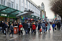 Last minute Christmas shoppers in Oxford Street, the main shopping district in the city centre of Swansea, Wales, UK. Monday 23 December 2019