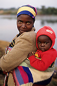 Mbati, Zambia. Mother with her daughter in red hat and jumper, slung in a knitted wrap on her back.