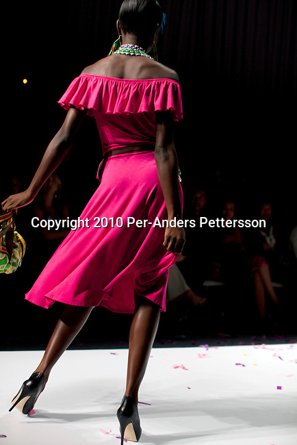 CAPE TOWN, SOUTH AFRICA - AUGUST 13: A model walks on the catwalk with one outfit from Stoned Cherrie, a fashion label, at the African Fashion International Cape Town fashion week on August 13, 2010, at the Cape Town International Convention Center, in Cape Town, South Africa. Stoned Cherrie is founded by Nkhensani Nkosi, age 37, a mother of four and a celebrated fashion designer, entrepreneur, television personality and an actress in South Africa. She launched her new collection Love Movement at this event. (Photo by Per-Anders Pettersson)