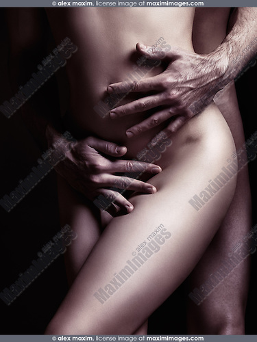 Sensual couple artistic nude closeup photo. Man hands embracing naked woman body. Black and white sepia toned.