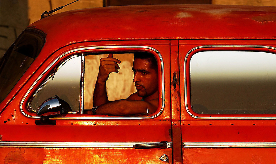 Journal photo by Ted Richardson:  4/10/2004  In a red hot American classic in the late-afternoon Havana swelter, a taxi driver motions for his customer.