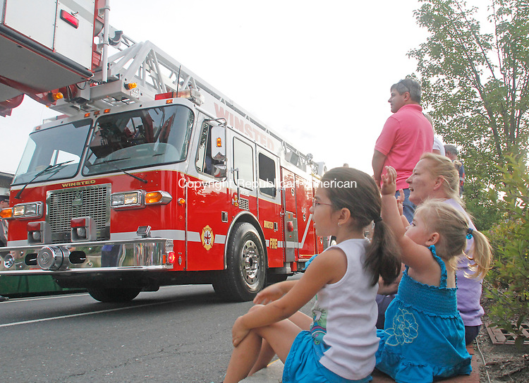 Winsted, CT-062513MK30 (from left) Sisters Myla and Cecila Olsen with their grandmother Debora Morey watch the fire apparatus pass by the judges stand during the 151st Winsted Fire Department Parade in Winsted on Saturday afternoon.  Thirty-nine departments entered into the event while thousands of people enjoyed watching as the firemen competed for trophies. Michael Kabelka / Republican-American.