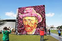 Nederland Amsterdam  2015 07 30.  Ter ere van de honderdvijfentwintigste sterfdag van Vincent van Gogh is op het Museumplein in Amsterdam een van de beroemde zelfportretten van de kunstenaar nagemaakt, door leden van de Zundertse corsobouwers. Het zelfportret bestaat uit een tableau van acht bij acht meter en bevat ongeveer 50.000 dahlia's. Zundert was de geboorteplaats van van Gogh.