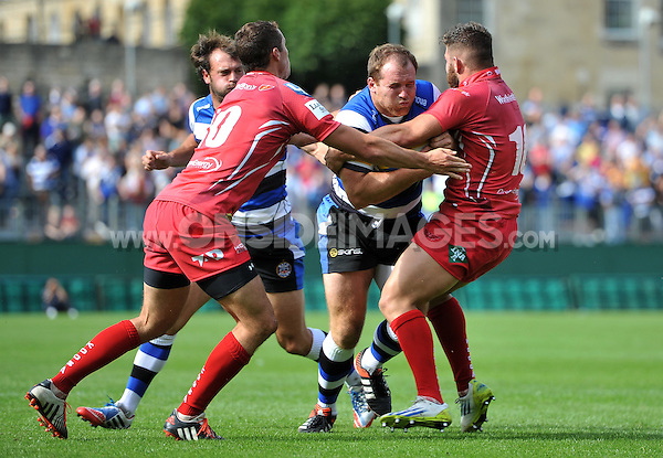 Henry Thomas takes on the Scarlets defence. Pre-season friendly match, between Bath Rugby and the Scarlets on August 16, 2014 at the Recreation Ground in Bath, England. Photo by: Patrick Khachfe / Onside Images