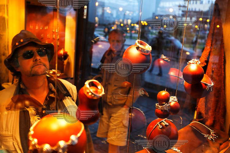 Tourists look at Inca-style jewellery displayed in a shop window. Inca culture has become a major attraction bringing tourists to the region...