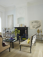 A painting by Mari Jose Marin and a pencil drawing by Philippe Segeral flank the fireplace in another living room which is furnished with vintage Chinoiserie-style armchairs