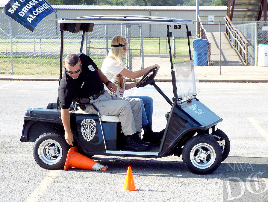 Photo by Randy Moll<br /> Sierra Holt, a senior at Gentry High School (right), accompanied by Gentry chief of police, Keith Smith, attempts to drive a police department golf cart around the cones while wearing goggles which simulate impaired vision due to alcohol or drug consumption on Sept. 7. The Fatal Vision exercise was to show students the dangers of driving while impaired by alcohol or drugs.