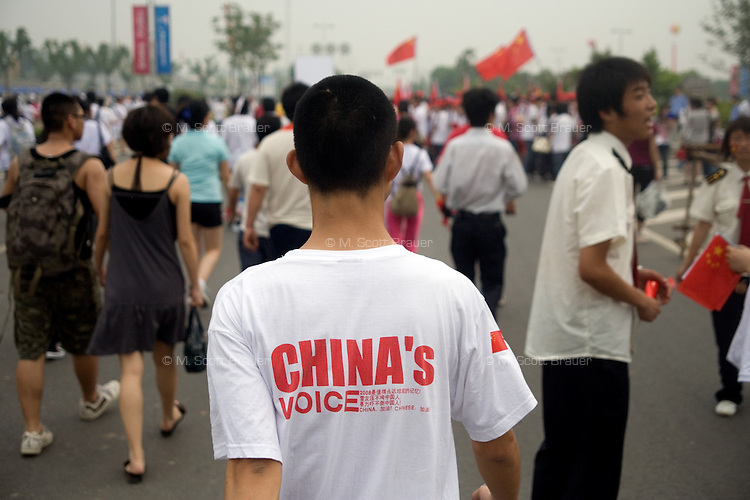 "A man wearing a nationalist shirt that says ""China's Voice"" walks through the crowd of spectators during the Nanjing, China, leg of the 2008 Olympic Torch Relay.  ."