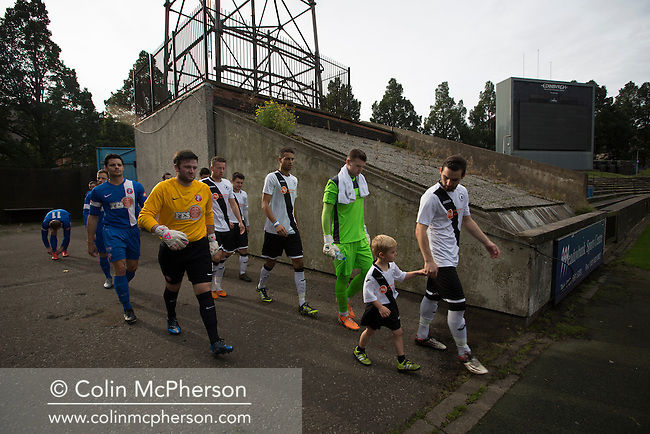 Both sets of players walking on to the pitch together at Meadowbank Stadium in Edinburgh, before Edinburgh City (in white) played host to Spartans in a Lowland League fixture. The host won the match 1-0 with a late goal by Ousman See, despite playing for the last 30 minutes with 10 men after Ross Allum was sent off. The wind kept the reigning champions side clear at the top of the league.