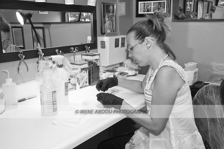 Tracy Baker, an apprentice piercer at a tattoo parlor in Rockland, Maine, prepares to pierce her mentor's chin in a practice session.