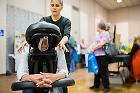 NWA Democrat-Gazette/CHARLIE KAIJO Mona Trembath of Denver, Colo. receives a back massage from Flor Roeder, owner and massage therapist of Touch Therapeutic Massage, Thursday, March 15, 2018 at Riordan Hall in Bella Vista. <br />