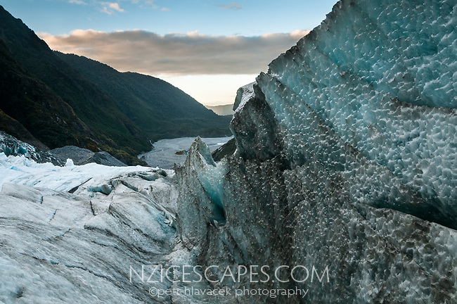 Looking along ice wave down into glacier valley from top of terminus of Franz Josef Glacier at sunset, Westland Tai Poutini National Park, West Coast, UNESCO World Heritage Area, New Zealand, NZ