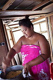 FRENCH POLYNESIA, Moorea. A woman wearing a sarong and cooking in her kitchen.