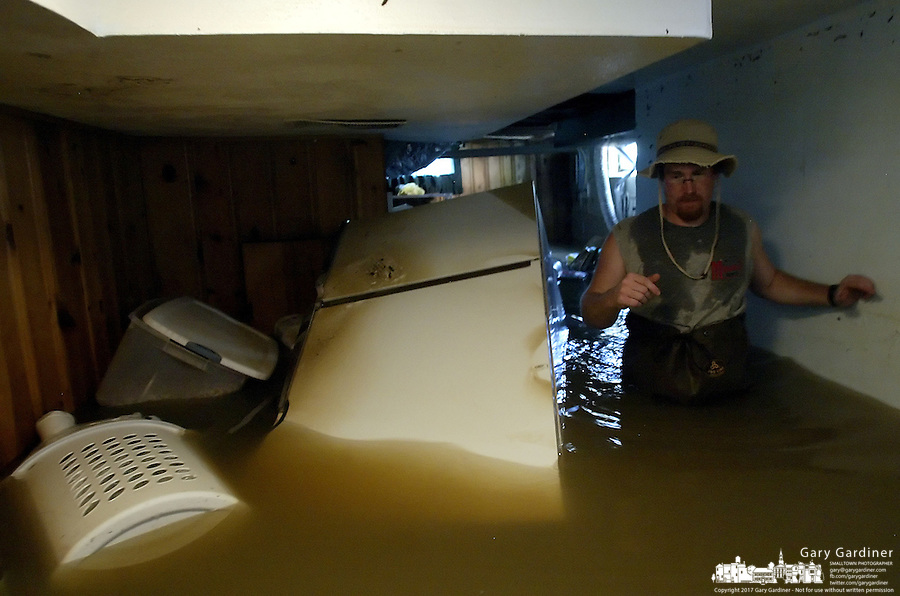 John Langenderfer wades through his basement looking to salvage some of his possessions as flood water from the Blanchard River starts to recede after heavy rains caused flooding Thursday, August 23, 2007, in Findlay, Ohio. The Blanchard River was close to 7 feet above flood stage at Findlay yesterday morning, the highest since a 1913 flood..