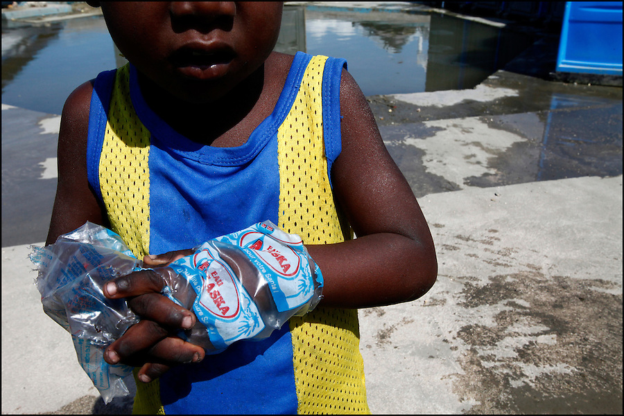 Nov 10, 2010 - Port-au-Prince, Haiti.A young resident of a tent city in the Cite Soleil area of Port-au-Prince, Haiti wears water bags as gloves in an effort, his older sister said, to avoid getting cholera, as other residents gather water from pipes just yards from portable toilets and flood waters from Hurricane Tomas Wednesday, November 10, 2010 as fears of a Cholera outbreak spread through the area just two days after cases of the infection were confirmed in the area, the poorest slum in Haiti's capital. Officials from the Pan American Health Organization warn that Haiti's cholera epidemic, spread primarily through consuming infected water and food, is likely to grow much larger in the wake of Hurricane Tomas.  (Credit Image: Brian Blanco)