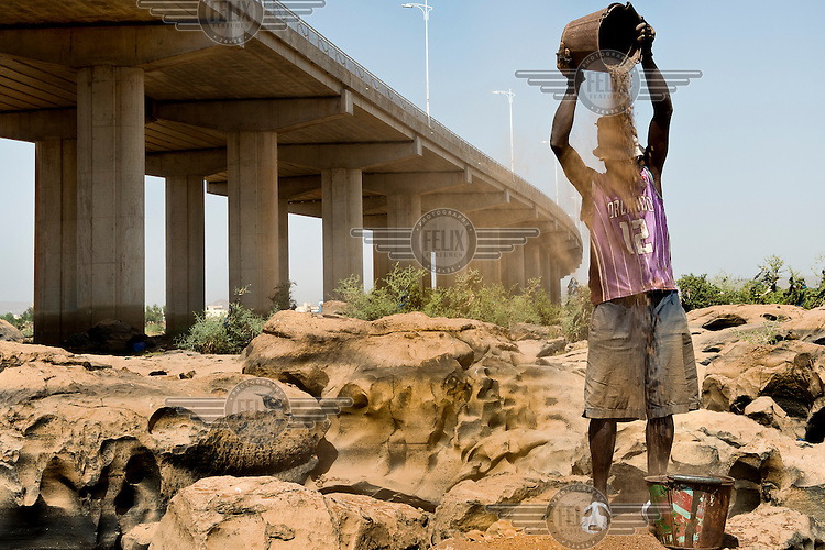 A man sifting sand beneath a Chinese built bridge spanning the River Niger. The bridge was opened in September 2011 and is the third crossing of the Niger in Bamako.