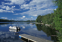 Vermont, VT, Boats reflecting in the calm water of Harvey's Lake in Barnet.