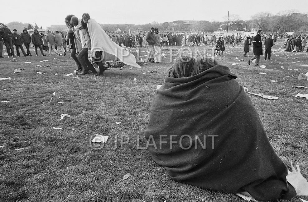 15 Nov 1969, Washington, DC, USA --- Protestors of the Vietnam War huddling in a blanket at the end of the Peace Moratorium on the Mall in Washington, DC on November 15, 1969. The Peace Moratorium 2nd is believed to have been the largest demonstration in US history with an estimated 20 to 30 million people involved. --- Image by © JP Laffont