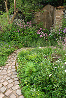 Stone garden bench in rustic country garden full of old-fashioned heirloom flowers, stone pavers in curving pathway, wide view . Board and batten door
