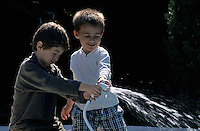 Two boys (11-13) playing with garden hose, smiling