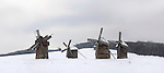 Ancient wooden windmills in a snow covered field Ukraine Eastern Europe Countryside winter scenic Horizontal orientation Panoramic
