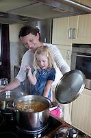 Polish mom helping daughter age 4 cook at stove making soup. Zawady Central Poland