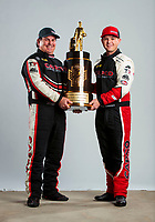 Feb 20, 2020; Chandler, Arizona, USA; NHRA top fuel driver Steve Torrence (right) poses for a portrait with his world championship trophy alongside father Billy Torrence during the Arizona Nationals at Wild Horse Pass Motorsports Park. Mandatory Credit: Mark J. Rebilas-USA TODAY Sports