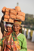 Delhi, India. Two women labourers carrying bricks on their heads.