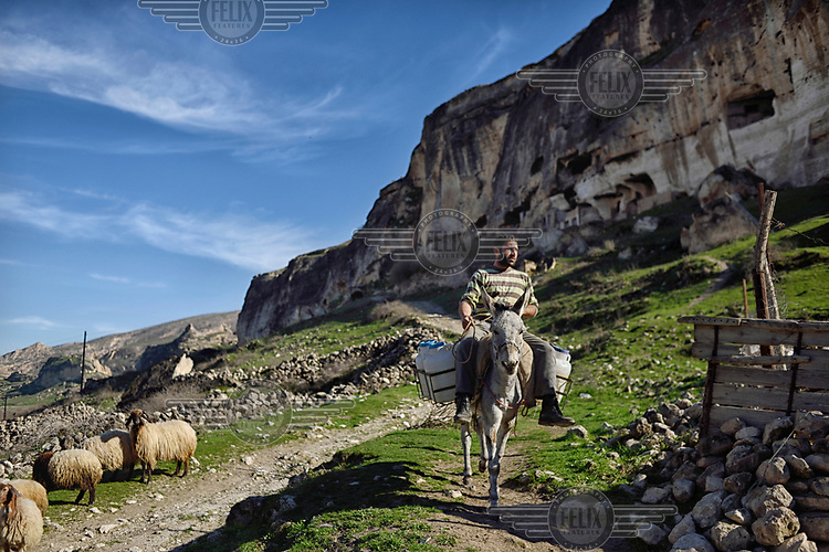 A man rides his donkey in Hasankeyf. 80% of the town will be submerged beneath 60 metres (200 feet) of water following the completion of the Ilisu hydroelectric dam, 96 kilometres (60 miles) downstream on the Tigris River. The reservoir created by the dam will be approximately of 313 km2 (121 sq mi) and will flood several villages as well as Hasankeyf.