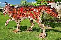 Wolf Sculpture called 'Between Dog and Wolf ' in St. Boniface Sculpture Garden at Office of the Festival du Voyageur. Saint Boniface<br /> Winnipeg<br /> Manitoba<br /> Canada