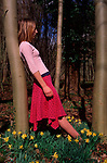 A911YE Young girl leaning against a tree with daffodils all around her feet and distant dark forest