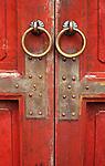 Red Doors 02 - Weathered red painted panelled wooden doors with metal door pull rings, Hue, Viet Nam