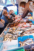 Street market merchant's stall with many different type of fish shopping ladies fighting to get the best pieces, fish on ice Sanary Var Cote d'Azur France