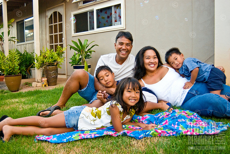 Local part Hawaiian family with mom, dad and three young children on grass in front of their home