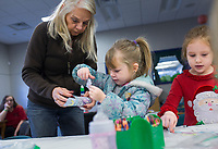 NWA Democrat-Gazette/CHARLIE KAIJO Joanna Page of Pea Ridge (from left) helps Maddie McCullum, 4, make a paper nut cracker with Eloise Sullivan, 4, of Rogers, Monday, December 2, 2019 during the Storytime Express early childhood development program at the Rogers Public Library in Rogers.<br /> <br /> Storytime Express is a traditional storytime for ages 3-5 years. Children read stories, sing songs, do movement rhymes and make a craft. Each week they focus on a different letter of the alphabet. Programs at the library will conclude during the week of Christmas and will resume again after the new year.