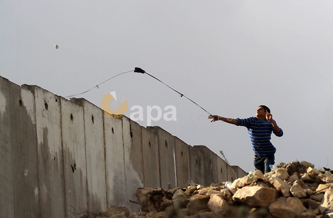 A Palestinian protester uses a sling shot to throw stones towards Israeli security forces during clashes following a protest against Israeli restrictions to Al-Aqsa Mosque in Jerusalem, at the Qalandia checkpoint near the West Bank city of Ramallah, November 14, 2014. Israel eased age restrictions for Friday prayers at Jerusalem's flashpoint Al-Aqsa mosque for a second straight week, allowing tens of thousands to attend despite high tensions following a wave of violence. Photo by Shadi Hatem