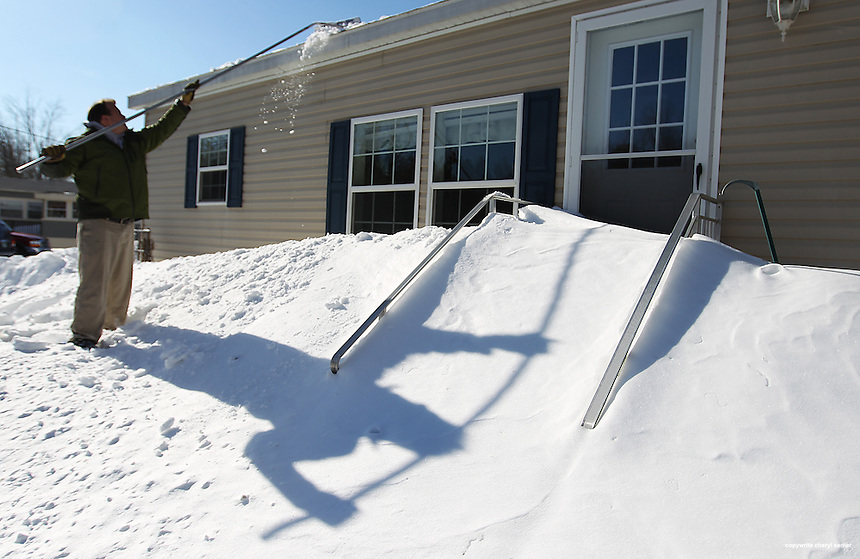 A large shadow plays off of the snow as Chris Huston cleans off of his roof in North Hampton, N.H., Sunday, Feb. 10, 2013.  (Portsmouth Herald Photo Cheryl Senter)