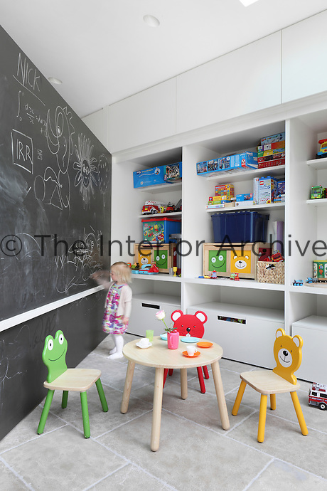 A large panel, recessed into the cupboards of the kitchen/dining area, folds out to create access to toys and a play area