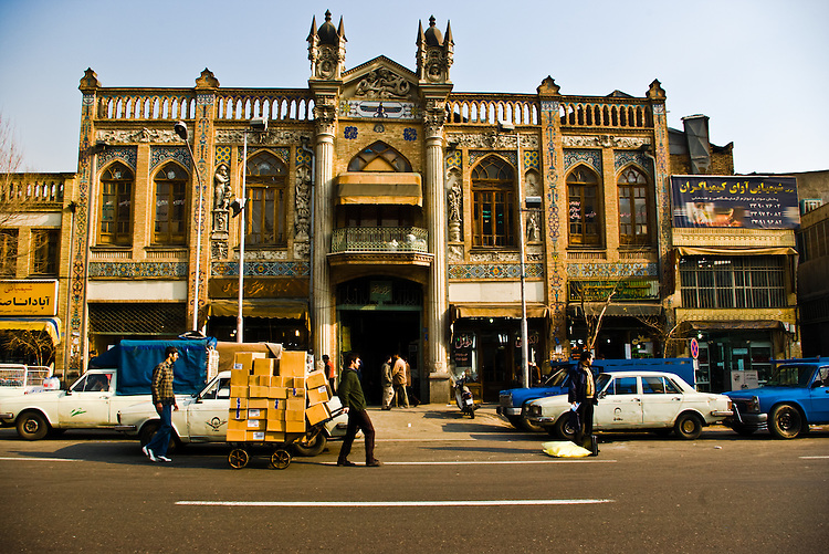 A Qajar-era monument stands by the bustling activity of goods being transferred from buyer to seller in the streets surrounding Tehran's grand bazaar.