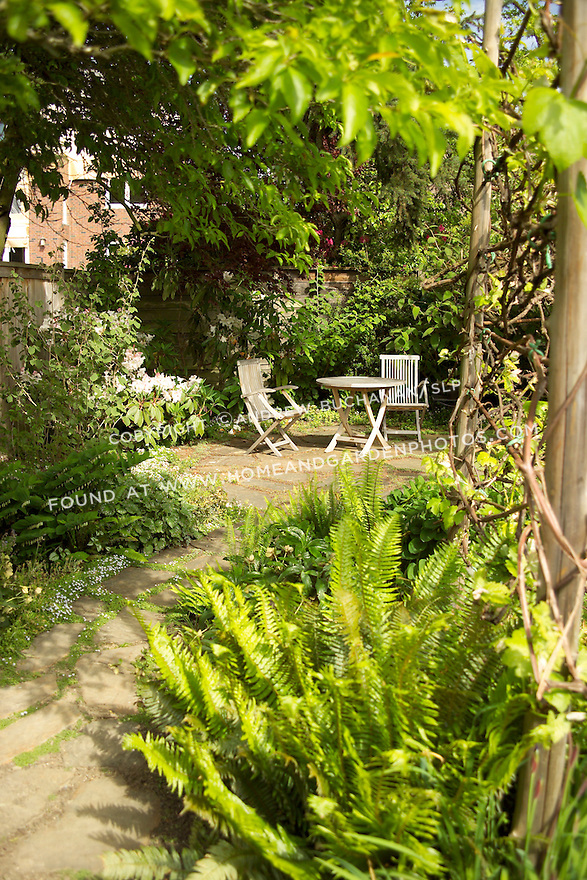 in the summer sunshine, two folding teak chairs sit on a small residential, backard patio accessed via a flagstone path bordered on both sides by lush gardens