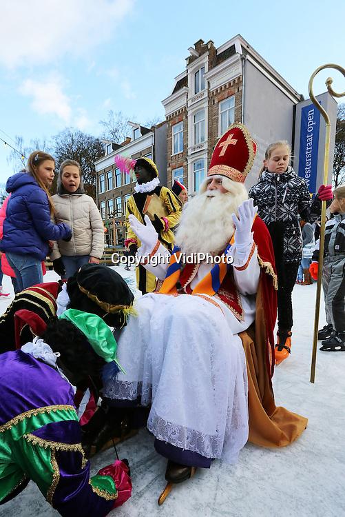 Foto VidiPhoto<br /> <br /> ARNHEM - Een historisch moment zaterdag voor de liefhebbers van Sinterklaas en de goedheiligman zelf. Voor het eerst in -volgens hem- 500 jaar bond St. Nicolaas weer zijn schaatsen onder, voor een schaatswedstrijd met zijn Pieten en -later- met de kinderen op het ijs. Vanzelfsprekend wist Sint de kolderieke Pieten ver voor te blijven. Sinterklaas was zaterdag eregast in het Nederlands Openluchtmuseum in Arnhem om de winter in het park officieel in te luiden. Tot en met 12 januari 2014 kunnen bezoekers in het Openluchtmuseum een ouderwetse winter beleven, inclusief schaatsplezier op de kunstijsbaan.