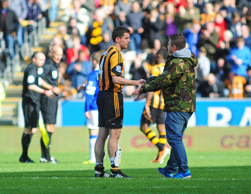 A spectator runs on to the pitch at the end of the game and shakes hands with Hull City's Alex Bruce<br /> <br /> Photographer Chris Vaughan/CameraSport<br /> <br /> Football - Barclays Premiership - Hull City v Everton - Sunday 11th May 2014 - Kingston Communications Stadium - Hull<br /> <br /> &copy; CameraSport - 43 Linden Ave. Countesthorpe. Leicester. England. LE8 5PG - Tel: +44 (0) 116 277 4147 - admin@camerasport.com - www.camerasport.com