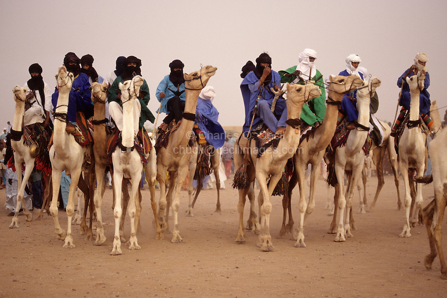 In-Gall, near Agadez, Niger - Tuaregs Parading Camels at Annual Cure Salé, Annual Gathering of Tuareg Nomads.  As is their custom, most of the men cover their mouths with the tagulmust, the Tuareg veil.