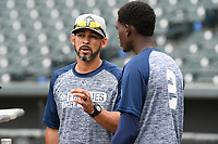 Hitting coach Luis Rivera (9) of the Columbia Fireflies, left, talks with Ronny Mauricio (2) during batting practice before a game against the Charleston RiverDogs on Friday, April 5, 2019, at Segra Park in Columbia, South Carolina. Charleston won, 6-1. (Tom Priddy/Four Seam Images)
