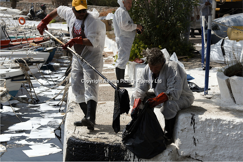 """Pictured: Specialist crew work to contain the oil spill that has reached the coast of Salamina, Greece<br />Re: An oil spill off Salamina island's eastern coast is spreading and has become """"an environmental disaster"""" according to local authorities in Greece.<br />The spill was caused by the sinking of the Aghia Zoni II tanker, carrying 2,200 metric tons of fuel oil and 370 metric tons of marine gas oil on Saturday, southwest of the islet of Atalanti near Psytalleia. According to reports, the coastline stretching from Kinosoura to the Selinia community has """"turned black"""" and authorities fear a new leak from the sunken ship.<br />According to the island's mayor, Isidora Papathanasiou, the weather """"turned on Sunday afternoon and brought the oil spill to Salamina."""""""