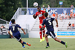 09 July 2014: Dallas' Hendry Thomas (HON) (in red) heads the ball over Carolina's Cesar Elizondo (CRC) (7) and Nazmi Albadawi (5). The Carolina RailHawks of the North American Soccer League played FC Dallas of Major League Soccer at WakeMed Stadium in Cary, North Carolina in the quarterfinals of the 2014 Lamar Hunt U.S. Open Cup soccer tournament. FC Dallas won the game 5-2.